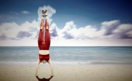 ビーチで女性逆立ち 写真素材
