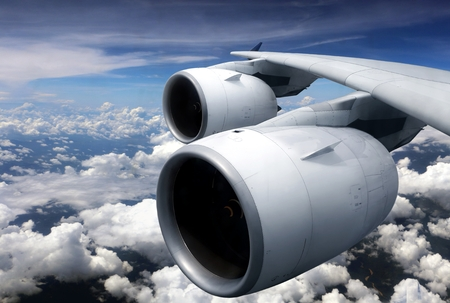 Airplane turbine engine from window view with cloudy sky