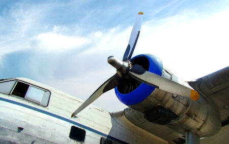 Old propeller airplane engine against cloudy blue sky