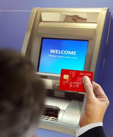 Men at ATM machine doing banking transaction 写真素材