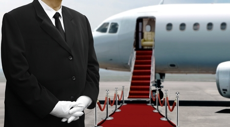 Airplane pilot standing on red carpet before departure