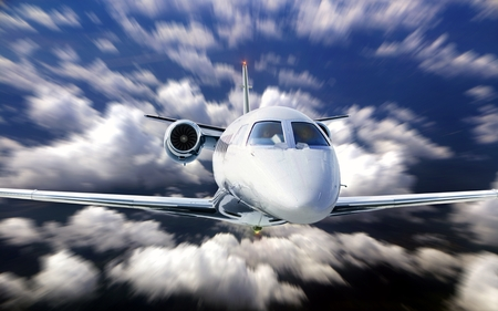 Private jet flying under cloudy blue sky