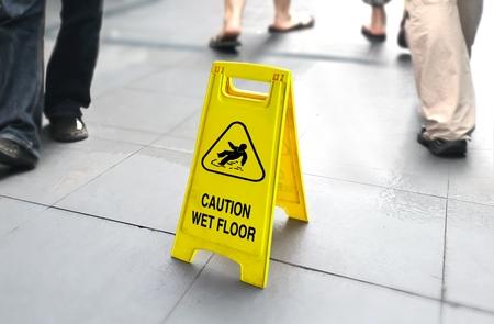 バック グラウンドで歩く人々 と濡れた床サイン