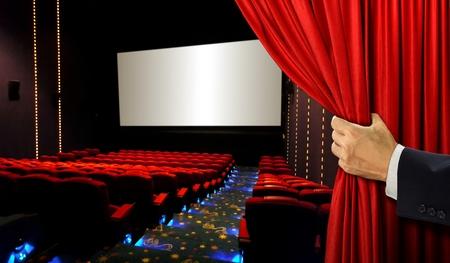 映画館の座席と赤いカーテンを開き手と空白の画面