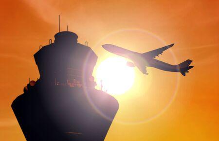 日没時に空港管制塔近くを飛んでいる飛行機