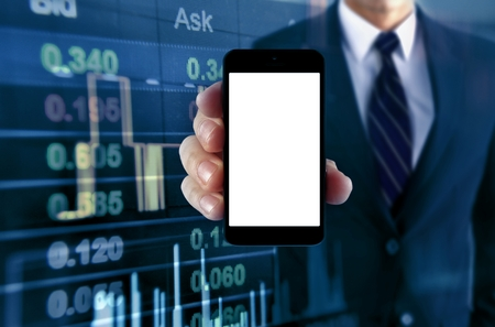 Man showing smartphone with stock chart background 写真素材