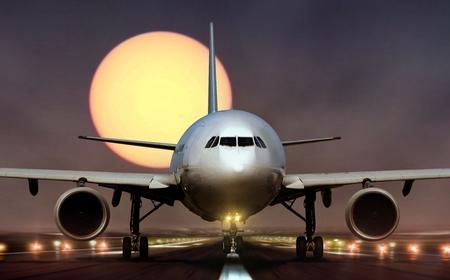 Airplane landing on runway during sunset