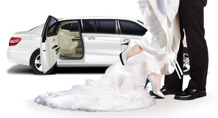 Groom and bride standing beside white limo 写真素材