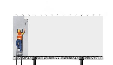 Man on ladder painting on billboard