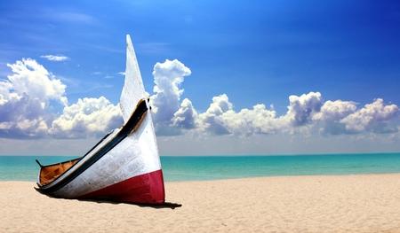 曇りの青空の下、ビーチで小さな木製ボート