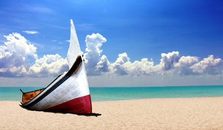 Small wooden boat at the beach under cloudy blue sky