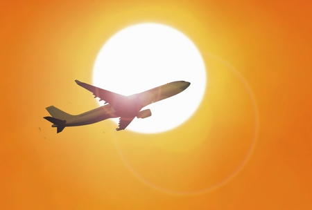 Airplane flying under sunset with yellow sky 写真素材