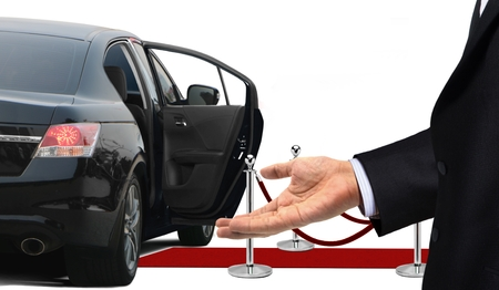 Driver standing with welcome gesture next to limousine