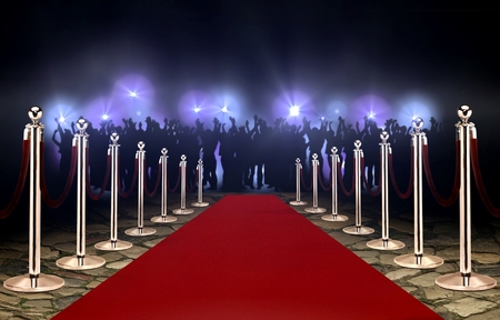 Czerwony dywan między barierami linowymi a tłumem