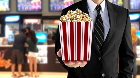 Man holding popcorn at movie counter