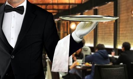 Male waiter serving in restaurant with people dining in background 写真素材