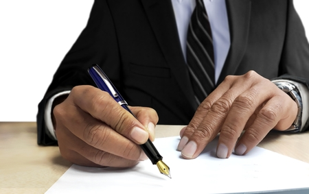 Man in suit writing on blank paper from front view angle 写真素材