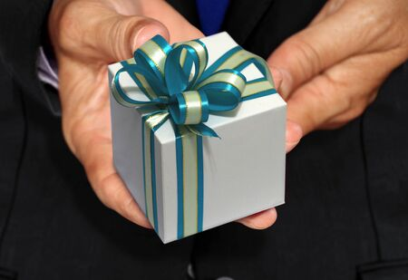 Hand holding white gift box with blue ribbon 写真素材