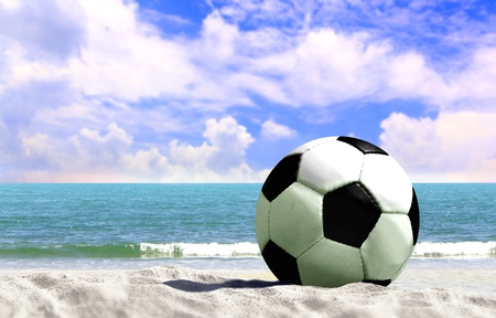 Soccer ball at the beach with cloudy blue sky
