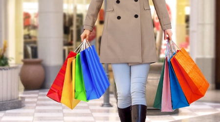 Women walking in a mall with handfull of shopping bags