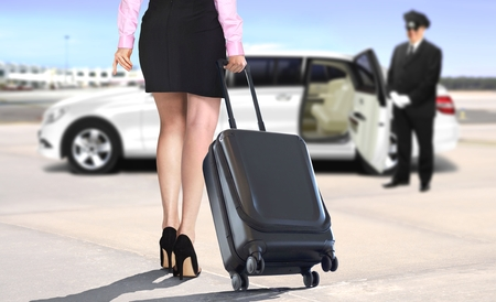 Women with suitcase at the airport leaving with white limo 写真素材
