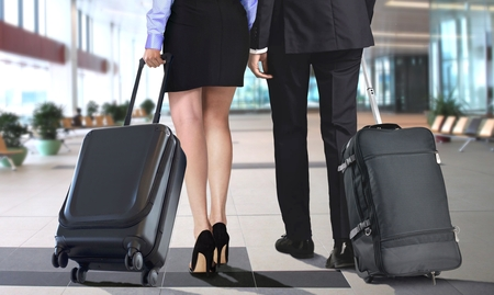 Man and Woman pulling suitcase at airport departure waiting area