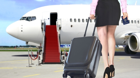 Woman pulling luggage boarding an airplane at the airport