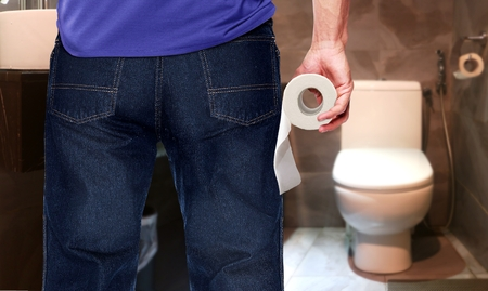 Man in a toilet holding tissue paper roll