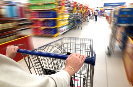 Women pushing trolley cart in supermarket 写真素材