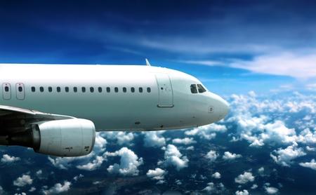 Airplane flying in cloudy sky below 写真素材