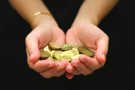 Hand with handful of coins over black background