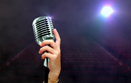 Hand holding microphone on stage under spotlights