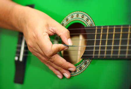 Hand playing guitar close up