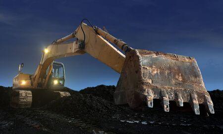 excavator digging at sunset 写真素材