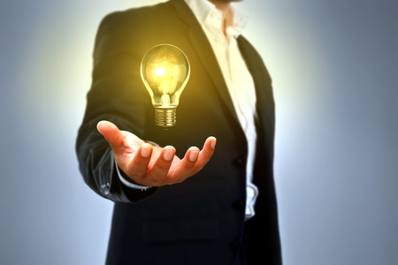 man holding bright light bulb