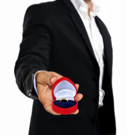 man holding with gold ring in red box