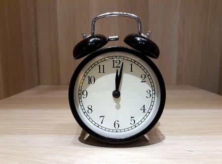 Retro alarm clock on wooden cabinet Stock Photo