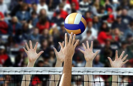 Punta de voleibol con las manos bloqueando la red