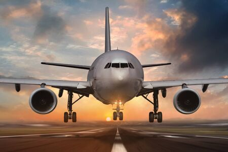Airplane landing on airport runways during sunset Stock Photo