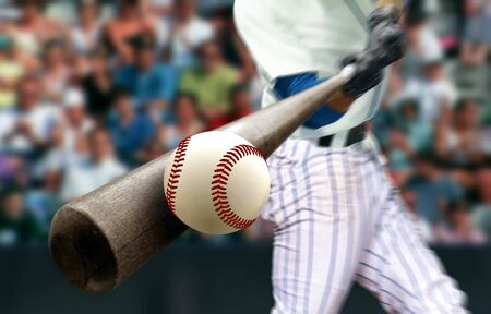 Baseball player hitting ball with bat in close up Foto de archivo