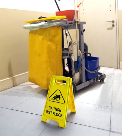 wet floor signage with cleaning tools in background