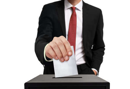 Man casting his vote into ballot box in close up over white background