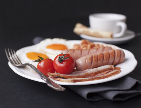 plate with English breakfast: fried eggs, beans, tomatoes, bacon, sausages and cup of coffee on black background.