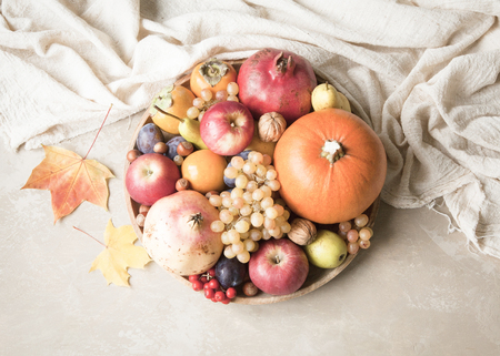 Autumn food concept. Fruits, vegetables and nuts on a wooden round tray on a light brown background. Stock fotó