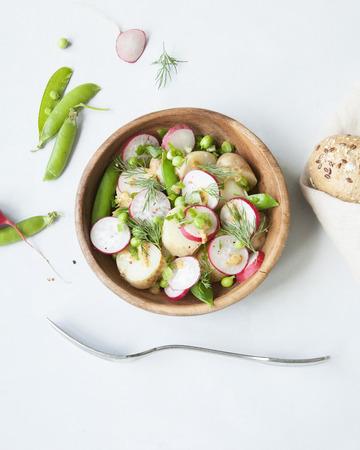 Un bol en bois de salade de légumes de printemps avec vinaigrette à la moutarde sur fond gris. Minimal.