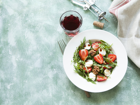 Fresh green salad with arugula, strawberry, cheese and hazel nuts. Stock Photo