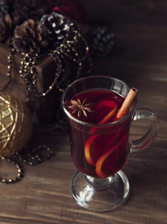Glass of hot mulled wine with orange, cinnamon and anise on dark wooden table. Christmas tree decoration of background.