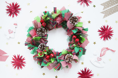 Christmas wreath made of colorful ribbons, cones, candy canes, poinsettia petals and artificial holly berries. White background. Flat lay.