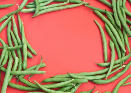 Green beans on red background  Stock Photo - 14878558