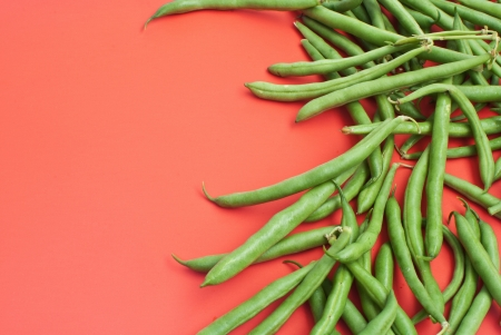 Green beans on red background  photo